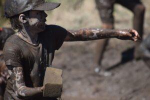 Youth throwing mud at mudslide day